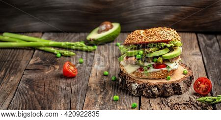 Homemade Burger With Grilled Chicken Fillet, Asparagus, Avocado, Tomatoes, Peas, Cheese And Tartar S