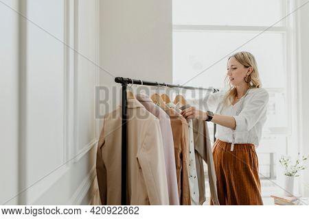Fashion stylist sorting the clothing rack