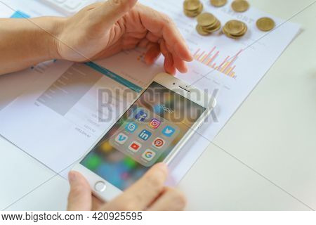 Chiang Mai, Thailand - May.16,2021: Man Using Apple Iphone With Icons Of Social Media On Business Re