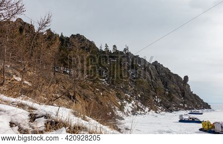 Trees And Dry Grass Grow On The Sandy Hillside. In The Distance, A Bizarre Granite Rock. Hovercraft