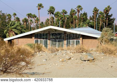 Arid Sandy Desert Besides An Retro Style Building With A 1950s Architectural Style And Palm Trees Be