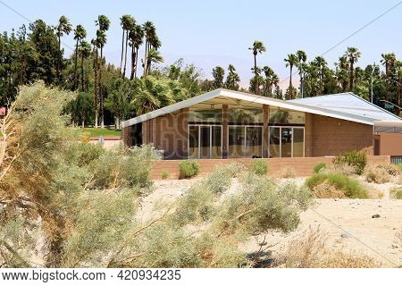 Retro Style Building With A 1950s Architectural Design Besides An Arid Desert Landscape With Manicur