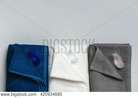 Three Terry Towels In Blue, White And Gray With Feathers. Flat Lay Top View With Copy Space For Text