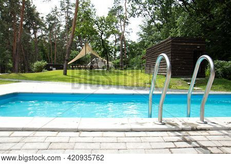 Swimming Pool With Stair. Clear And Blue, Clear Water In The Pool. Grab Bars Ladder In The Blue Swim