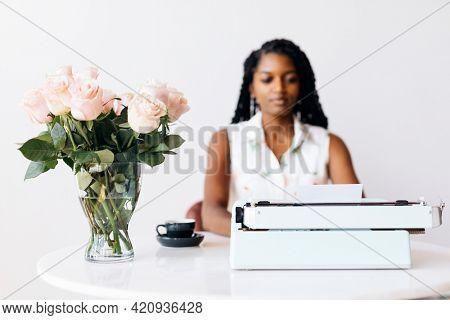 Woman typing on retro light blue pastel typewriter