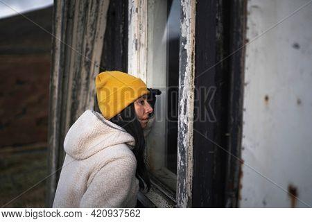 Woman looking through an A-Frame cabin window