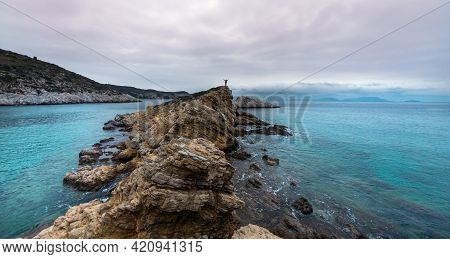 Girl With A Backpack Stands On A Mountain By The Sea. The Traveler Looks At The Sea, Standing On The