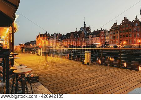 Gdansk Night City Riverside View, Wooden Embankment And Street Cafe On It. Facades Of Old Medieval H
