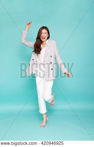 Attractive Beautiful Asian Woman Standing And Hands Up Raised Arms From Happiness Isolated On Green