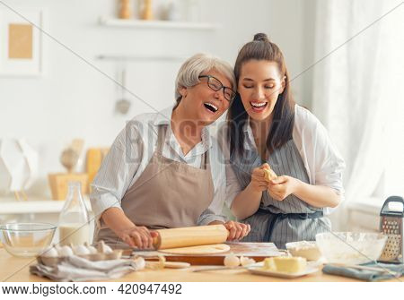 Happy family in the kitchen. Mother and her adult daughter are preparing pastry.