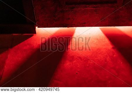 A Mystical And Dangerous Red Light Through A Gap Under The Door. Fabulous Atmosphere Of Mysteries An