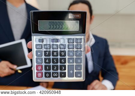 Man Holding Calculator In Hand. Business Man Showing Value On Calculator.