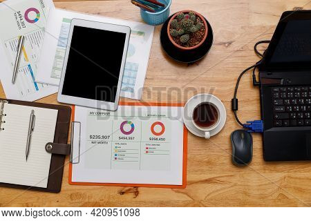 Top View Of Digital Tablet With Business Paper Chart Or Graph  And Etc On Wooden Table. Wooden Offic