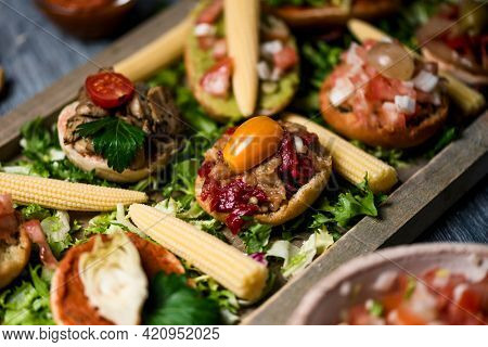 closeup of some different vegan appetizers, with different toppings, served on a bed of chopped lettuce on a wooden tray, placed on a gray rustic wooden table
