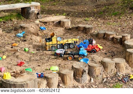 Plastic Toys In The Sandbox On The Playground In The Park. Toys Abandoned And Forgotten In The Sandb