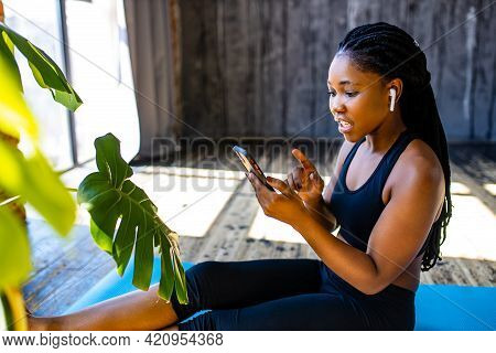 African American Woman In Black Sporty Bra With Yoga On Mat Listening An Audio Meditate Mantra