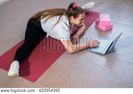 Young Caucasian Fat Woman Doing Bends On A Sports Mat And Watching A Training Video On A Laptop. A C