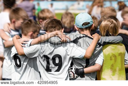 Happy Sporty Team Huddling With Coach. Children Football Team Standing Together In A Circle Before T