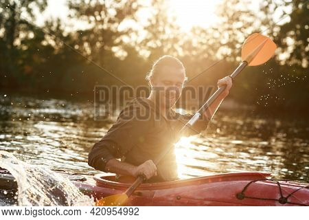Caucasian Young Man Looking Cheerful, Holding A Paddle, Kayaking In A Lake Surrounded By Nature On A