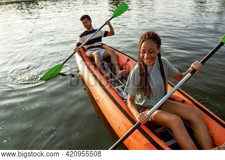 Excited Young Couple Enjoying Paddling Kayak On A River Together On A Summer Afternoon. Kayaking, Tr