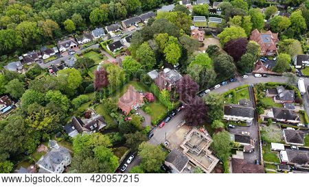 Aerial View Of Some Large Detached Houses Set Amongst Woodland