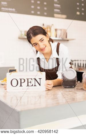 Vertical Frame Of Beautiful Caucasian Barista Woman Looks At Left Side While Placing Elbows And Show
