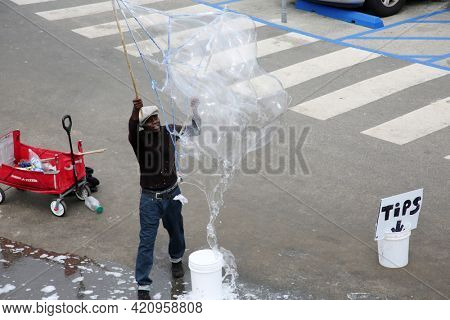 May 14, 2021 Santa Monica California, USA: A man blows giant soap bubbles from the parking lot for tips and the enjoyment of tourist.  Editorial Use.