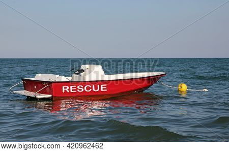 Red Motorboat In The Middle Of The Sea To Rescue Swimmers With The Large Rescue Text