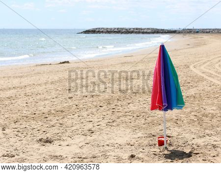Isolated Umbrella In The Middle Of The Beach With No Person And The Sea  In Late Summer