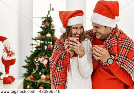 Young hispanic couple wearing christmas hat and covering with blanket. Standing with smile on face drinking cofffee at home.
