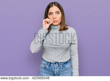 Young beautiful woman wearing casual turtleneck sweater mouth and lips shut as zip with fingers. secret and silent, taboo talking