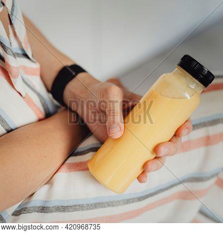 Woman holding cold-pressed detox juice bottle mockup