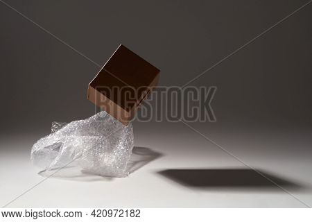 Close-up Of Cardboard Box And Bubble Wrap On Dark Background