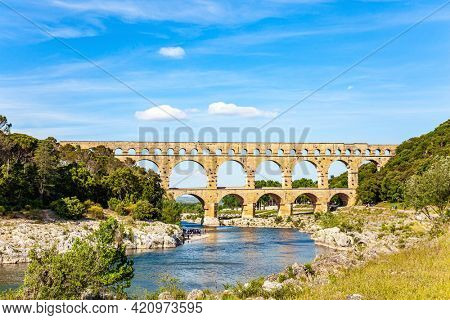 The Pont du Gard is the tallest Roman aqueduct. Picturesque antique bridge - aqueduct. Interesting trip to France. The shallow Gardon River in a bright sunny day
