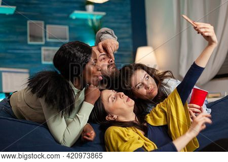 Group Of Mixed Race People Taking Pictures With Phone While Sitting On Couch In Living Room Spending