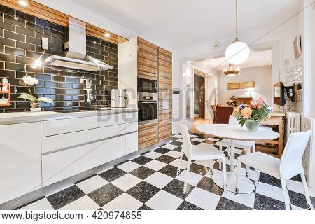 Round Table With Flowers And Chairs Located On Tiled Floor Near Contemporary Cupboards And Appliance