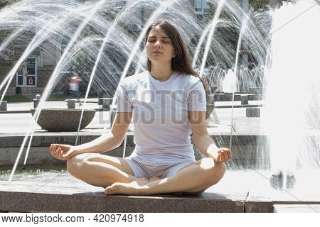 Beautiful Brunette Woman In White Clothes Meditates Near A Fountain On The Street In The City. Yoga
