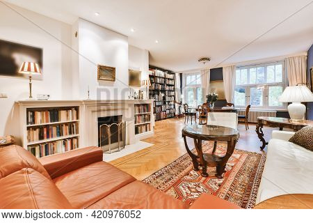 Comfortable Sofas And Round Table Located Near Fireplace With Bookshelves In Elegant Living Room In