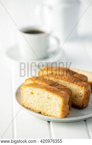 Sliced sponge dessert. Sweet sponge cake on white table.