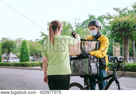 Male Courier With Bicycle Delivered Shopping Yellow Bag To The Client.courier Delivery Food Service