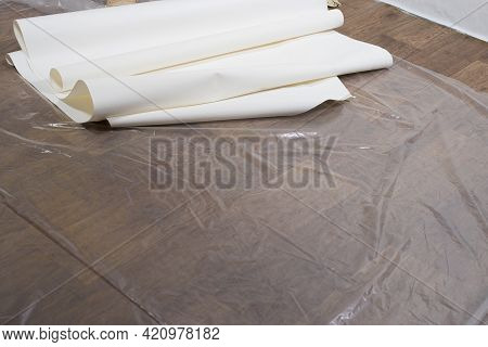 Rolls Of White Wallpaper On The Floor During Renovation. Wallpaper Gluing, Place For Text.