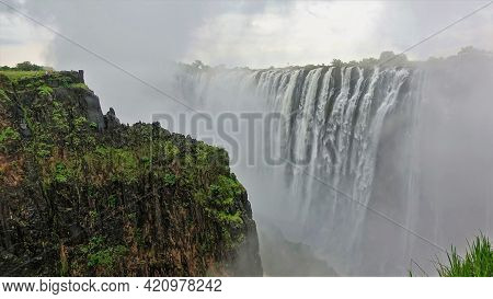 A Thick Fog From The Collapsing Streams Of Water Stands Over The Gorge. In The Foreground Is A Wet R