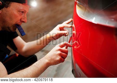 Car Service Worker Put Anti Gravel Film On A Red Car Body At The Detailing Vehicle Workshop. Car Pro