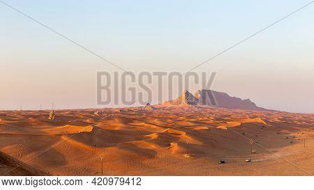 Panorama Of Sunset Over Fossil Rock Mountain Ridge And Golden Desert Dunes, Sharjah, United Arab Emi