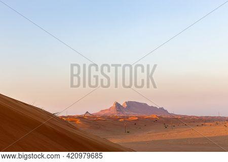 Sunset Over Fossil Rock Mountain Ridge And Golden Desert, Sharjah, United Arab Emirates.