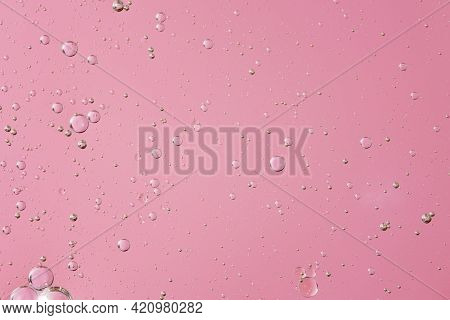 Oil With Bubbles On Light Pink Coral Monochrome Background. Abstract Space Background. Soft Selectiv