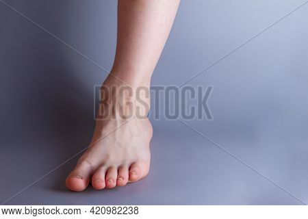 One Leg Of A 7-year-old Baby Boy On A Gray Background. Copy Space.