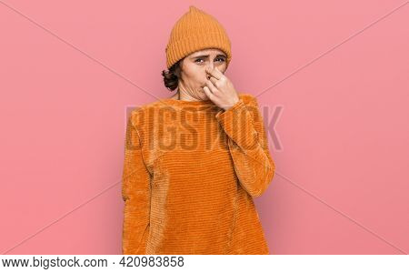 Young hispanic woman wearing casual clothes and wool cap smelling something stinky and disgusting, intolerable smell, holding breath with fingers on nose. bad smell