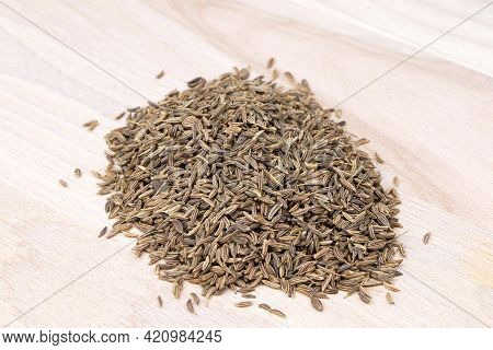 Cumin Isolated On A Wooden Background. Caraway Seeds. Heap Of Cumin.