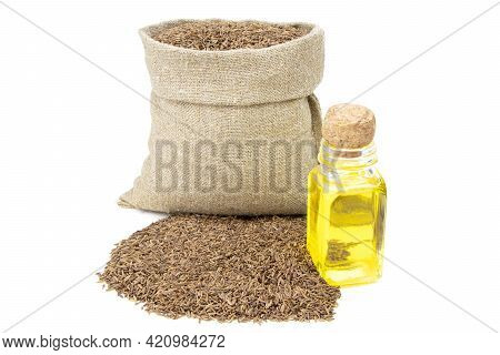 Cumin Essential Oil. Glass Bottle Of Cummin Oil. Caraway In A Sack Of Isolated On A White Background